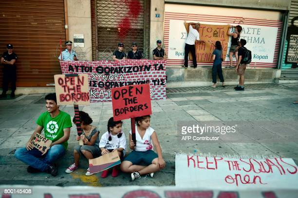 Refugee children hold up a placard reading 'Open the borders' as they sit in front of a mock fence with the slogan 'They secure the borders we secure...