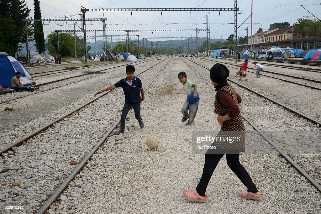 Refugee children plat football on the rails in the of old Idomeni train station near tents located on the rails on May 1'st, 2016 in Idomeni refugee camp. Humanitarian conditions in the camp are deteriorating as many thousands of migrants are still located in the makeshift refugee camp, located at the Greece-Macedonia border, waiting for the border to re-open.