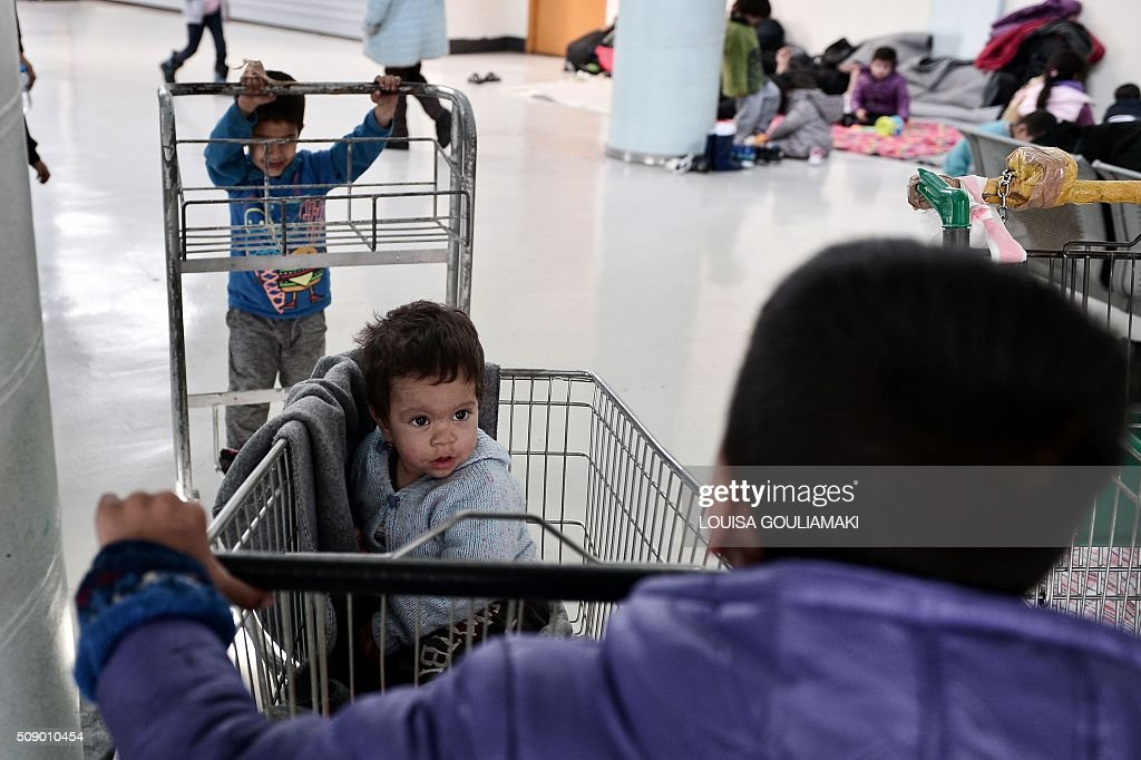 Refugee children play with carts inside a passenger terminal at the port of Piraeus near Athens on Febuary 8, 2016, where dozens of refugee and migrant families live temporarily , prior being able to travel towards the borders. Streams of people fleeing conflict or poverty continue to make the often perilous journey from Turkey across the Mediterranean and through the Balkans, despite cold winter weather, in the hope of starting new lives in more prosperous European countries. / AFP / LOUISA GOULIAMAKI