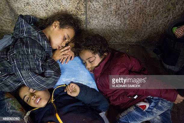 Refugee children rest as they wait to get on a train from Gyor to Hegyeshalom in Hungary on September 19 2015 During the night they were transported...