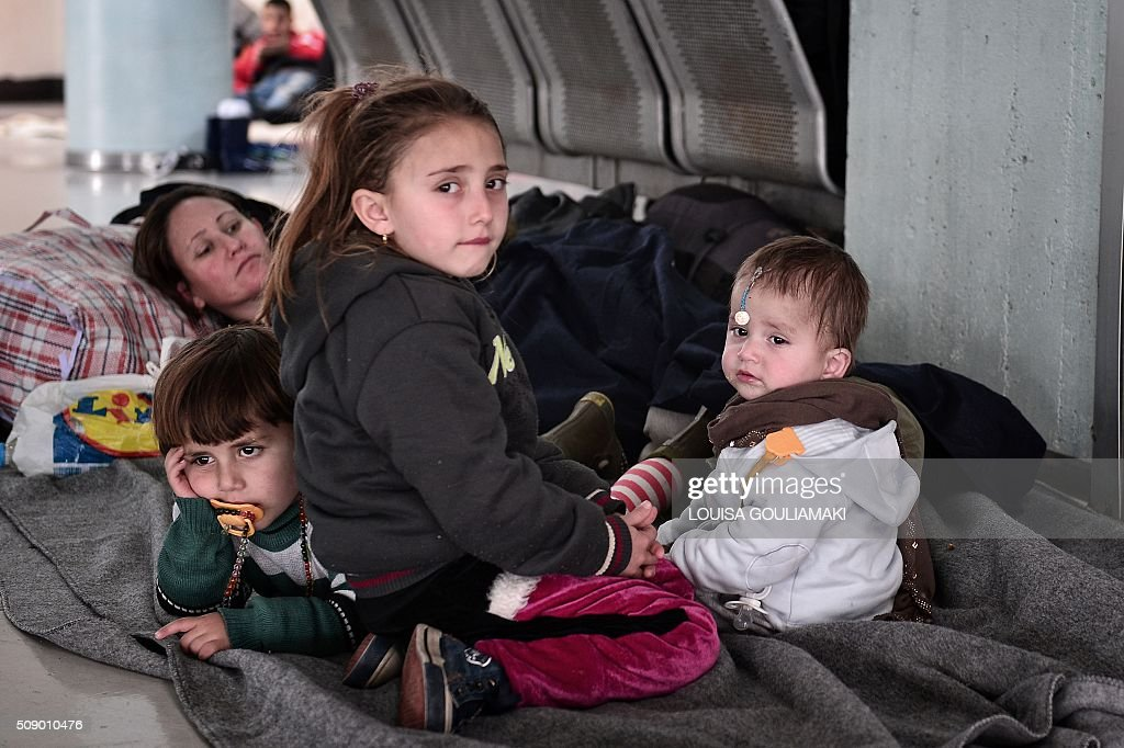 Refugee children rest at their shelter inside a passenger terminal at the port of Piraeus near Athens on Febuary 8, 2016 , where dozens of refugee and migrant families live temporarily, prior being able to travel towards the borders. Streams of people fleeing conflict or poverty continue to make the often perilous journey from Turkey across the Mediterranean and through the Balkans, despite cold winter weather, in the hope of starting new lives in more prosperous European countries. / AFP / LOUISA GOULIAMAKI