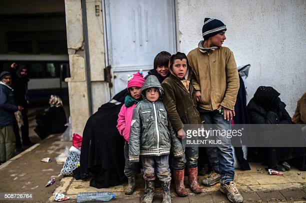 Refugee children wait near the Turkish border crossing gate as Syrians fleeing the northern embattled city of Aleppo wait on February 6 2016 in Bab...