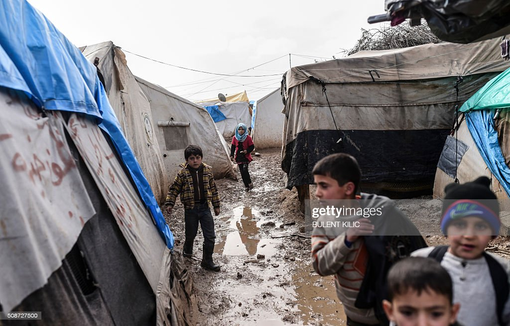 Refugee children walk between tents at a camp near the Turkish border crossing gate as Syrians fleeing the northern embattled city of Aleppo wait on February 6, 2016 in Bab-Al Salam, near the city of Azaz, northern Syria. Thousands of Syrians were braving cold and rain at the Turkish border Saturday after fleeing a Russian-backed regime offensive on Aleppo that threatens a fresh humanitarian disaster in the country's second city. Around 40,000 civilians have fled their homes over the regime offensive, according to the Syrian Observatory for Human Rights monitor. / AFP / BULENT KILIC