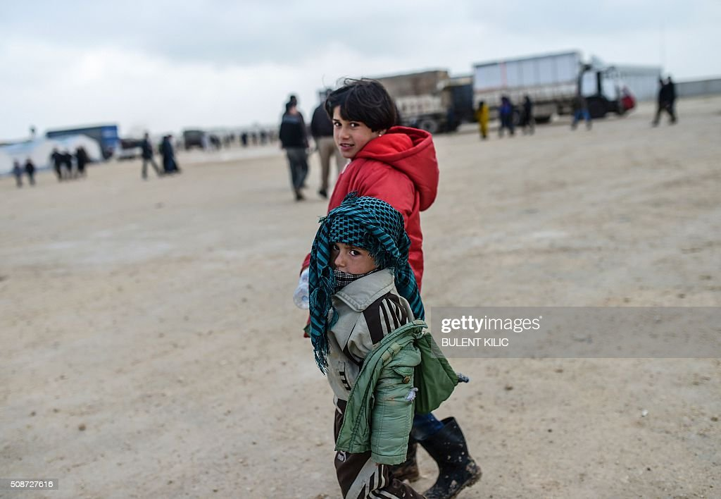 Refugee children walk in a camp near the Turkish border crossing as Syrians fleeing the northern embattled city of Aleppo wait on February 6, 2016 in Bab-Al Salam, near the city of Azaz, northern Syria. Thousands of Syrians were braving cold and rain at the Turkish border Saturday after fleeing a Russian-backed regime offensive on Aleppo that threatens a fresh humanitarian disaster in the country's second city. Around 40,000 civilians have fled their homes over the regime offensive, according to the Syrian Observatory for Human Rights monitor. / AFP / BULENT KILIC
