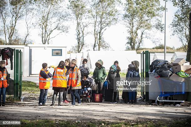 Refugee families are waiting with their luggages to climb into a bus afterleaving the 'Jules Ferry' center reception in Calais on November 3 2016...
