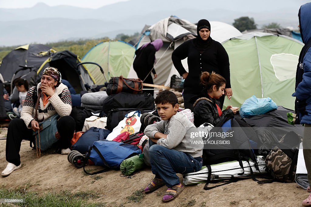 A refugee family sits in front of their tent as they wait to be transferred to reception centres, during an evacuation operation by Greek police forces of the makeshift camp at the Greek-Macedonian border, near the village of Idomeni, on May 24, 2016. In an operation which began shortly after sunrise on May 24, hundreds of Greek police began evacuating the sprawling camp which is currently home to 8,400 refugees and migrants, among them many families with children, an AFP correspondent said. At its height, there were more than 12,000 people crammed into the site, many of them fleeing war, persecution and poverty in the Middle East and Asia, with the camp exploding in size since Balkan states began closing their borders in mid February in a bid to stem the human tide seeking passage to northern Europe. / AFP / POOL / YANNIS