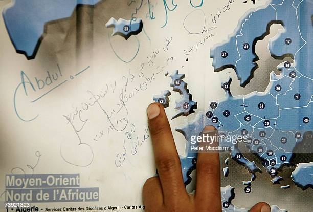 A refugee from Afghanistan points to a map of Europe displaying hand written messages from fellow migrants on April 18 2007 in Calais France Many who...