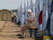 A refugee from eastern Ukraine looks on as she sits in a refugee camp near the Russian city of Donets'k Rostov region about 15 kilometers from the...