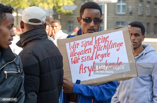A refugee from Eritrea holds a poster reading 'We are not illegal refugees We are legal asylumseekers' during a demonstration against the German...