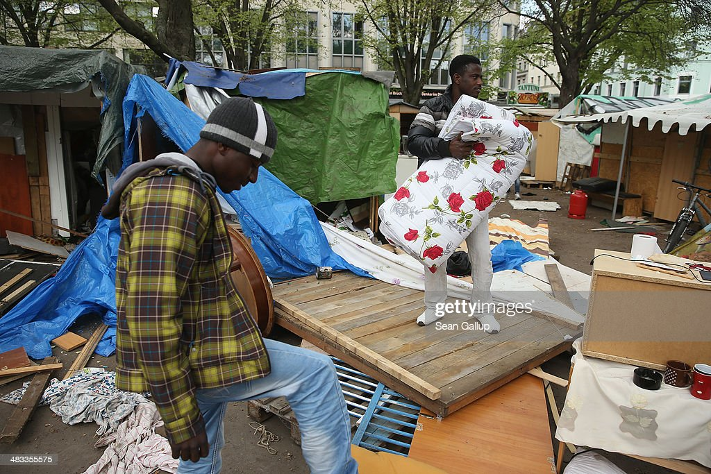 A refugee from Ghana (R), who said he will remain despite a deal struck by others with city authorities, folds a mattress amongst remains of huts that were being torn down at a temporary, city-tolerated refugee camp at Oranienplatz in Kreuzberg district on April 8, 2014 in Berlin, Germany. Refugees, many of them from Africa who came to Germany via Lampedusa, began dismantling their shelters today after many of them agreed to a deal with city authorities to move to a renovated hostel. Not all of the several hundred refugees, some of whom have been living at the Oranienplatz camp almost a year, have agreed to the deal, and while some said they will go elsewhere, some insist they will stay, despite a city order to vacate.