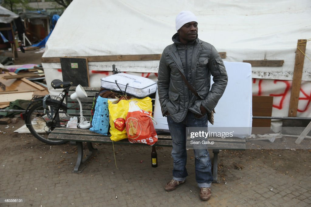 A refugee from Liberia who has not agreed to a deal with city authorities to move to a new shelter stands with his belongings near huts that were being torn down at a temporary, city-tolerated refugee camp at Oranienplatz in Kreuzberg district on April 8, 2014 in Berlin, Germany. Refugees, many of them from Africa who came to Germany via Lampedusa, began dismantling their shelters today after many of them agreed to a deal with city authorities to move to a renovated hostel. Not all of the several hundred refugees, some of whom have been living at the Oranienplatz camp almost a year, have agreed to the deal, and while some said they will go elsewhere, some insist they will stay, despite a city order to vacate.