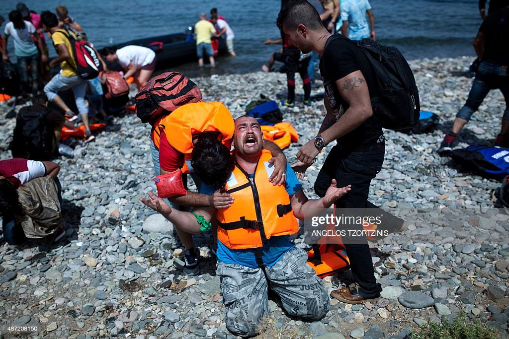 A refugee from Syria prays after arriving on the shores of the Greek island of Lesbos aboard an inflatable dinghy across the Aegean Sea from from...