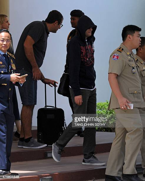 A refugee held under Australian custody in the Central Pacific island of Nauru is escorted by Cambodian police following his arrival at the Phnom...