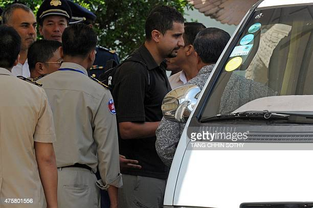 A refugee held under Australian custody in the Central Pacific island of Nauru is escorted to a waiting vehicle by Cambodian police following his...