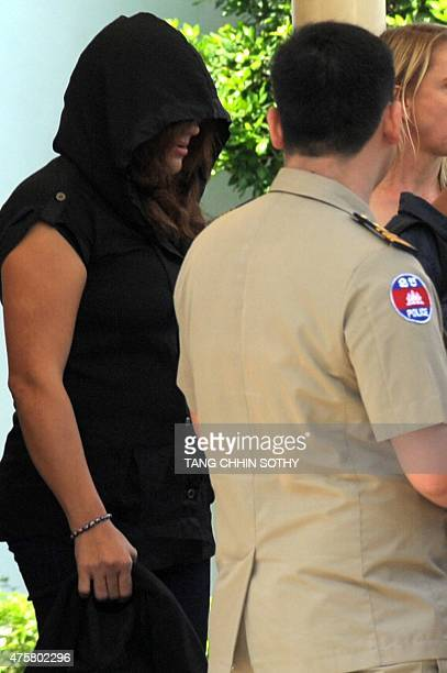 A refugee held under Australian custody in the Central Pacific island of Nauru is escorted by Cambodian police following her arrival at the Phnom...