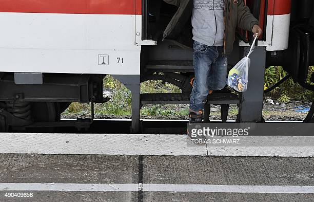 A refugee holds a bag with belongings at the Schoenefeld airport train station in Schoenefeld while arriving with a special train on September 28...