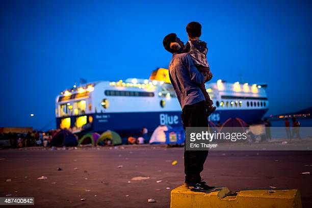 A refugee holds a child near a ferry at the port of Mytilini on September 9 2015 in Lesbos Greece Greece has been overwhelmed this year by record...