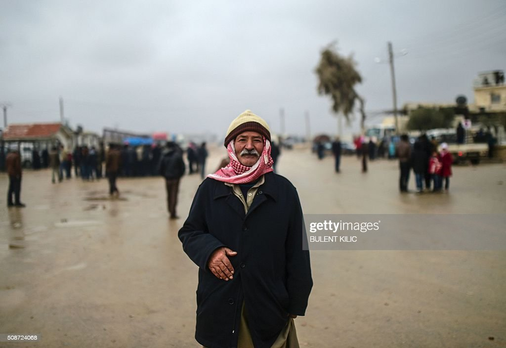 A refugee is pictured near the Turkish border crossing gate as Syrians fleeing the northern embattled city of Aleppo wait on February 6, 2016 in Bab-Al Salam, near the city of Azaz, northern Syria. Thousands of Syrians were braving cold and rain at the Turkish border Saturday after fleeing a Russian-backed regime offensive on Aleppo that threatens a fresh humanitarian disaster in the country's second city. Around 40,000 civilians have fled their homes over the regime offensive, according to the Syrian Observatory for Human Rights monitor. / AFP / BULENT KILIC
