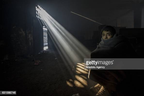 A refugee is seen wrapped in a blanket at a derelict warehouse where refugees took shelter in Belgrade Serbia on January 12 2017 Despite the help of...