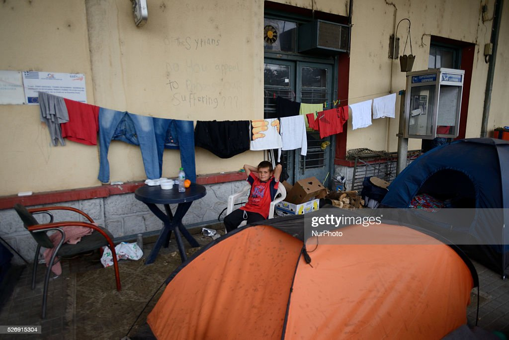 A refugee kid sits near tents and laundry on the dock in the old Idomeni train station on May 1'st, 2016 in Idomeni refugee camp. Humanitarian conditions in the camp are deteriorating as many thousands of migrants are still located in the makeshift refugee camp, located at the Greece-Macedonia border, waiting for the border to re-open.