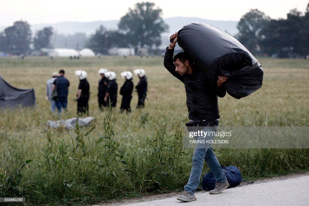 A refugee man carries his belongings during an evacuation operation by police forces of a makeshift migrant camp at the border at the Greek-Macedonian border near the village of Idomeni, on May 24, 2016. In an operation which began shortly after sunrise on May 24, hundreds of Greek police began evacuating the sprawling camp which is currently home to 8,400 refugees and migrants, among them many families with children, an AFP correspondent said. At its height, there were more than 12,000 people crammed into the site, many of them fleeing war, persecution and poverty in the Middle East and Asia, with the camp exploding in size since Balkan states began closing their borders in mid February in a bid to stem the human tide seeking passage to northern Europe. / AFP / POOL / Yannis KOLESIDIS