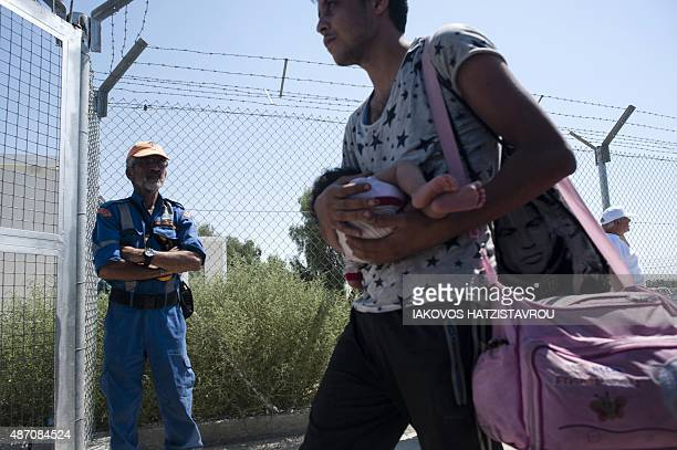 A refugee man fleeing the war in Syria holds a baby as he arrives at the Kokkinotrimithia refugee camp West of Nicosia in Cyprus on September 6 2015...