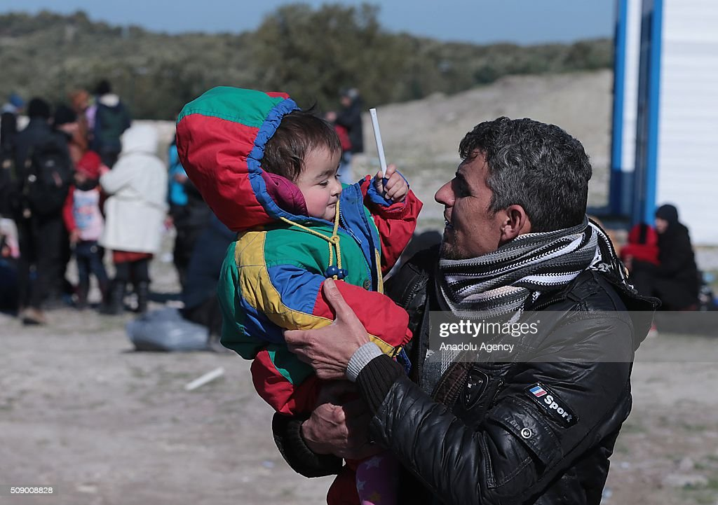 Refugee man holds his child on the coast as Turkish gendarmerie captures around 700 refugees, who were trying to reach Lesbos Island of Greece, in operations conducted at 3 different bays, namely Pissa, Bahceli and Candarli, in Dikili district of Izmir, Turkey on February 8, 2016.