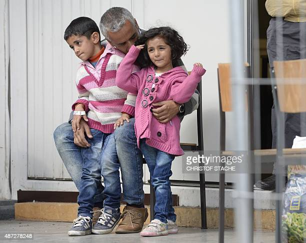 A refugee man holds two children while waiting to be processed at the first registration point for migrants of the German federation police in...