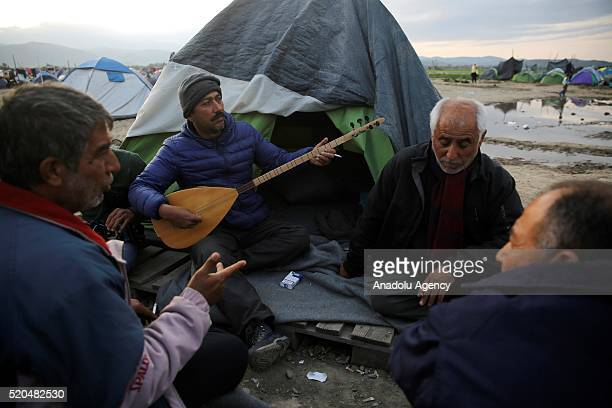 A refugee man plays 'saz' as they wait at a makeshift refugee camp in the Idomeni village of Greece near the Macedonian border on April 12 2016...