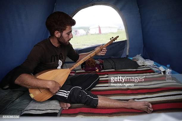 Refugee man plays the saz inside a tent as the refugees try to continue their daily life at Idomeni refugee camp in Greece on May 20 2016