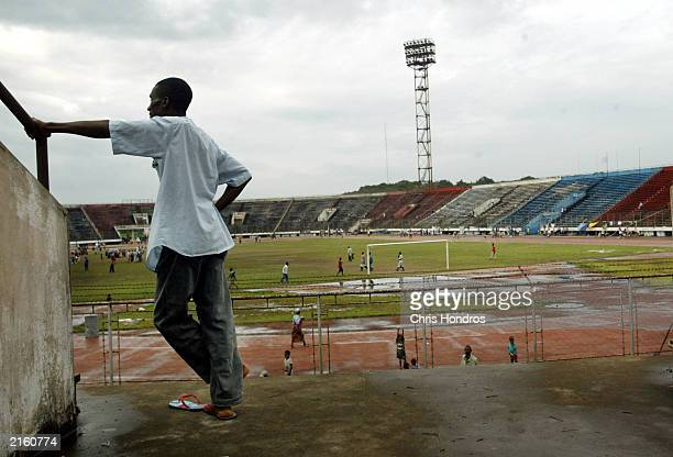 A refugee man stands on the walkway of a sports stadium July 14 2003 on the outskirts of Monrovia Liberia Thousands of internally displaced refugees...