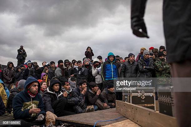 Refugee men form the audience as actors from Shakespeare's Globe perform Hamlet to migrants at the Good Chance Theatre Tent in the Jungle Refugee...