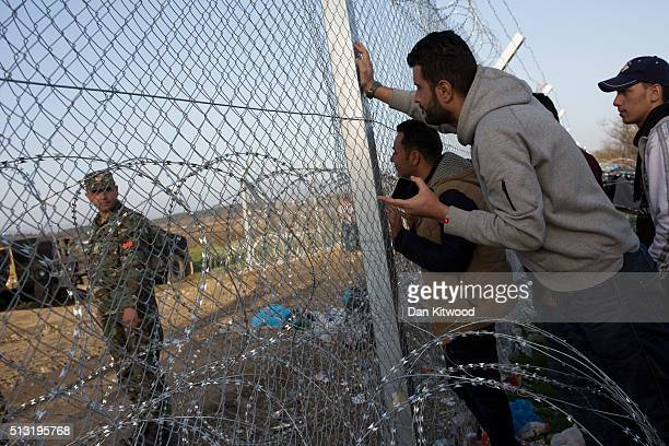 Refugee men talk to a Macedonian soldier at the other side of the fence at the GreekMacedonia border on March 01 2016 near Idomeni Greece The transit...