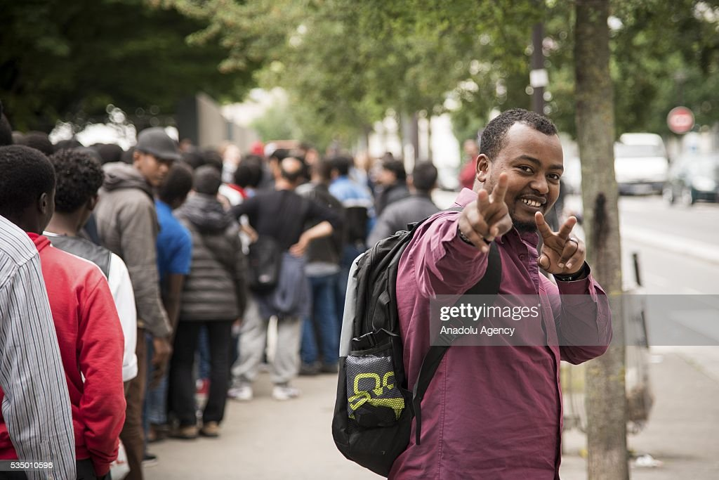 A refugee poses as other refugees wait in a queue for food distribution as they live in harsh conditions at a makeshift camp set at the Jardin d'Eole in Paris on May 28, 2016.