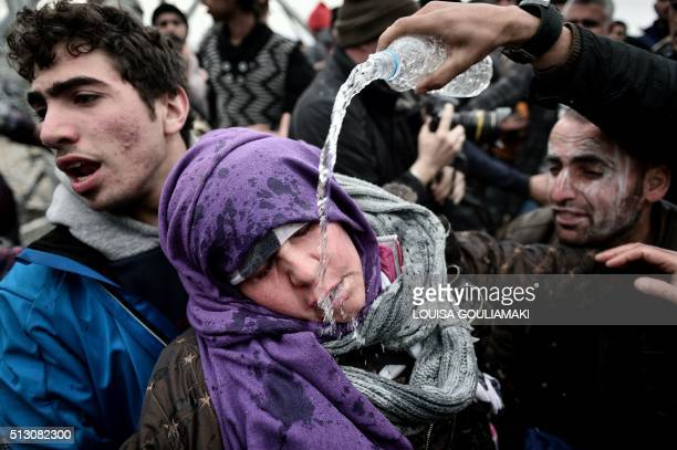 TOPSHOT A refugee pour water over a woman who collapsed because of losing her child in a panic move after Macedonian police used tear gas against...