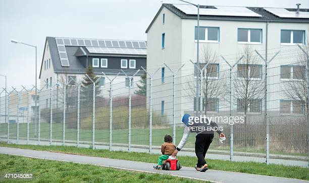 A refugee pushes his son on a bobbycar in a refugee center on April 17 2015 in Schneeberg Germany AFP PHOTO / DPA / PETER ENDIG GERMANY OUT