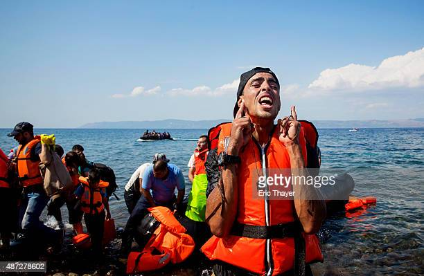 A refugee reacts after coming ashore near the village of Skala Sikamineas on September 8 2015 in Lesbos Greece More than 230000 people have landed on...