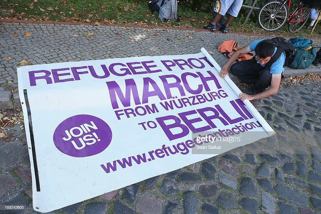 A refugee rolls up a protest banner after a brief rally before continuing with other refugees and supporters during their protest march across nearly 600km from Wuerzburg to Berlin on October 2, 2012 in Bad Belzig, Germany. Approximately 25 refugees who are seeking political asylum are marching to protest the conditions under which they live in Germany. Asylum seekers in Germany are by law prohibited from working and their ability to travel is very restricted. The group expects to arrive in Berlin on October 6.