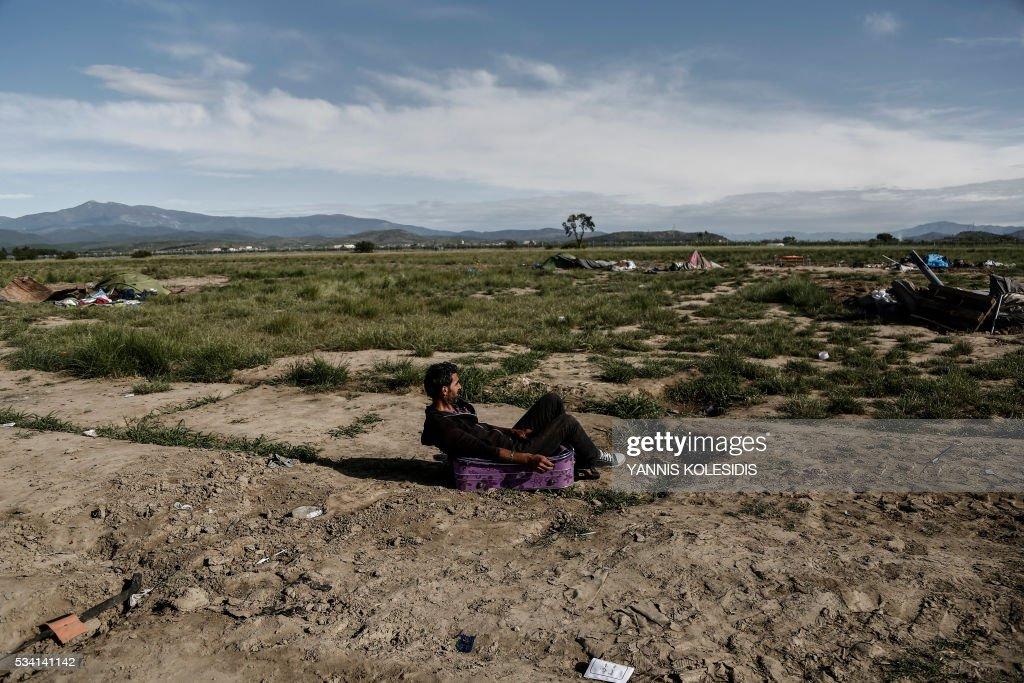 A refugee sits on his luggage watching during a police operation to clear the refugee and migrant camp at the border between Greece and Macedonia near the village of Idomeni, northern Greece on May 25, 2016. Greek police restarted an operation to move migrants out of Idomeni, the squalid tent city where thousands fleeing war and poverty have lived for months. The migrants and refugees on May 24 were bussed to newly opened camps near Greece's second city Thessaloniki, about 80 kilometres (50 miles) to the south. / AFP / POOL / Yannis KOLESIDIS