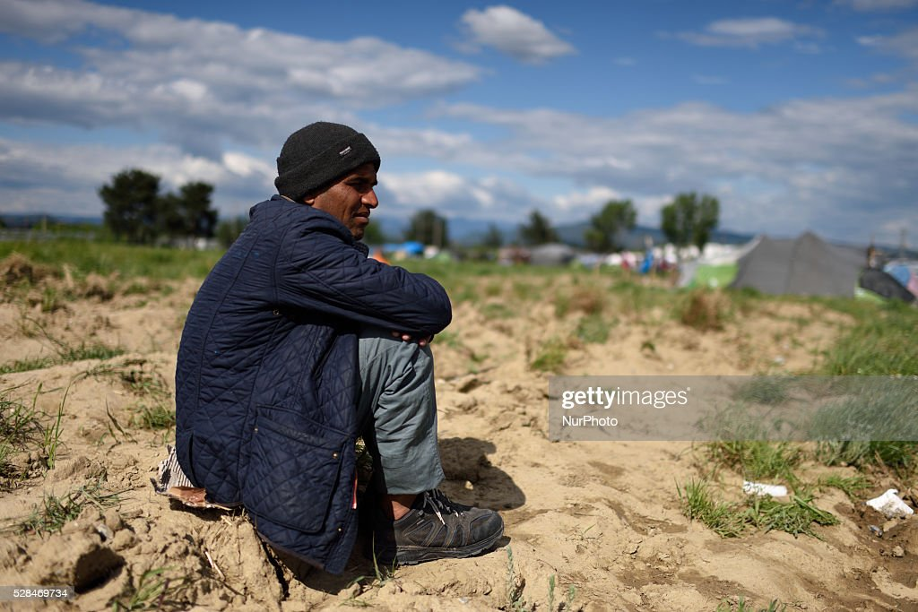 A refugee sits on the ground in a field just next to Idomeni refugee camp on May 5'th, 2016. Thousands of migrants are still located in the makeshift refugee camp, located at the Greek Macedonian border, waiting for the border to re-open.