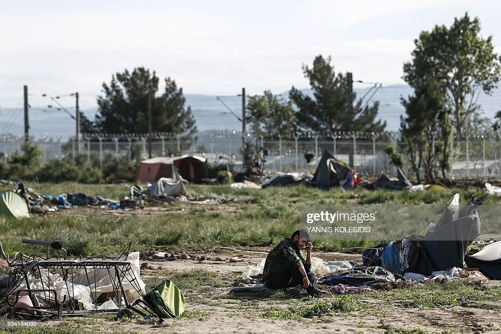 A refugee sits on the ground near destroyed tents during a police operation to clear a makeshift camp for refugees and migrants at the border between Greece and Macedonia near the village of Idomeni, northern Greece on May 25, 2016. Greek police restarted an operation to move migrants out of Idomeni, the squalid tent city where thousands fleeing war and poverty have lived for months. The migrants and refugees on May 24 were bussed to newly opened camps near Greece's second city Thessaloniki, about 80 kilometres (50 miles) to the south. / AFP / POOL / YANNIS