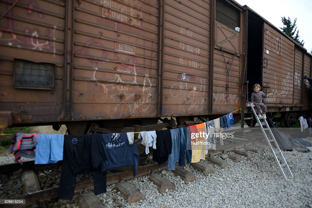 A refugee steps out of an abandoned train cabin, used as a shelter, in the old Idomeni train station on May 1'st, 2016 in Idomein refugee camp. Humanitarian conditions in the camp are deteriorating as many thousands of migrants are still located in the makeshift refugee camp, located at the Greece-Macedonia border, waiting for the border to re-open.