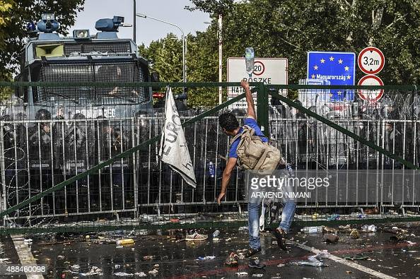 A refugee throws a bottle of water towards Hungarian riot police after they used water cannon to push back refugees at the Hungarian border with...