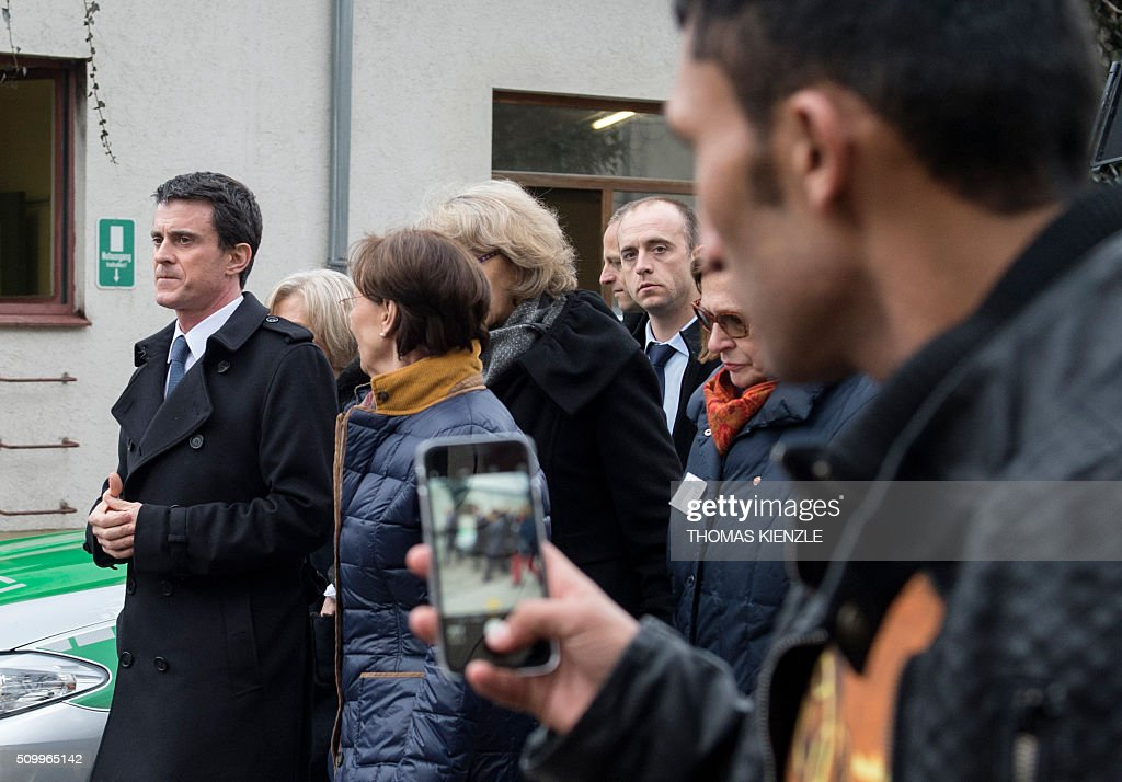 A refugee tries to make a video of French Prime Minister Manuel Valls (L) as he visits the refugee camp Bayernkaserne (Bavaria barracks) in Munich, southern Germany, on February 13, 2016. / AFP / THOMAS KIENZLE