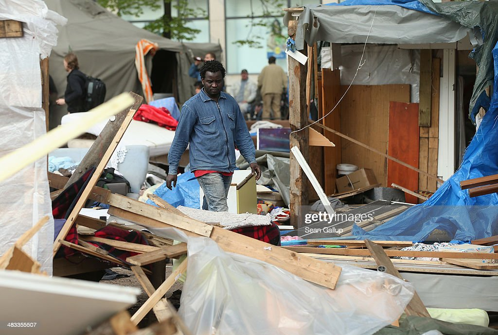 A refugee walks among the remains of huts that were being torn down at a temporary, city-tolerated refugee camp at Oranienplatz in Kreuzberg district on April 8, 2014 in Berlin, Germany. Refugees, many of them from Africa who came to Germany via Lampedusa, began dismantling their shelters today after many of them agreed to a deal with city authorities to move to a renovated hostel. Not all of the several hundred refugees, some of whom have been living at the Oranienplatz camp almost a year, have agreed to the deal, and while some said they will go elsewhere, some insist they will stay, despite a city order to vacate.