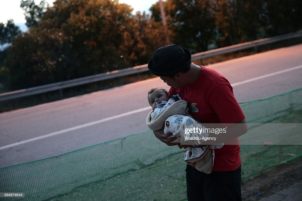 A Refugee with his baby, escaping from the evacuation in Idomeni, is seen as they wait at another refugee camp near Idomeni, Greece on May 25, 2016.
