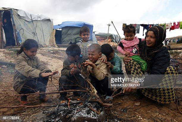 A refugee woman and children warm up around a fire at a camp housing Syrian families who fled their war torn country on January 8 2015 in the village...