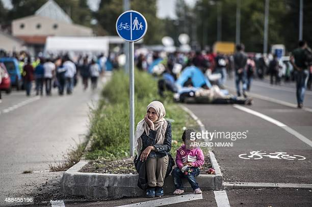 A refugee woman and her child sit on the side of a road at the Hungarian border with Serbia near the town of Horgos on September 16 2015 Europe's...