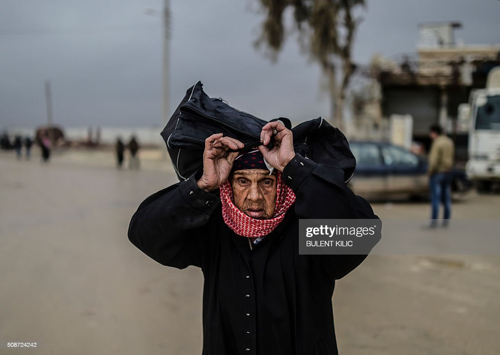 A refugee woman carries her belongings near the Turkish border crossing gate as Syrians fleeing the northern embattled city of Aleppo wait on February 6, 2016 in Bab-Al Salam, near the city of Azaz, northern Syria. Thousands of Syrians were braving cold and rain at the Turkish border Saturday after fleeing a Russian-backed regime offensive on Aleppo that threatens a fresh humanitarian disaster in the country's second city. Around 40,000 civilians have fled their homes over the regime offensive, according to the Syrian Observatory for Human Rights monitor. / AFP / BULENT KILIC