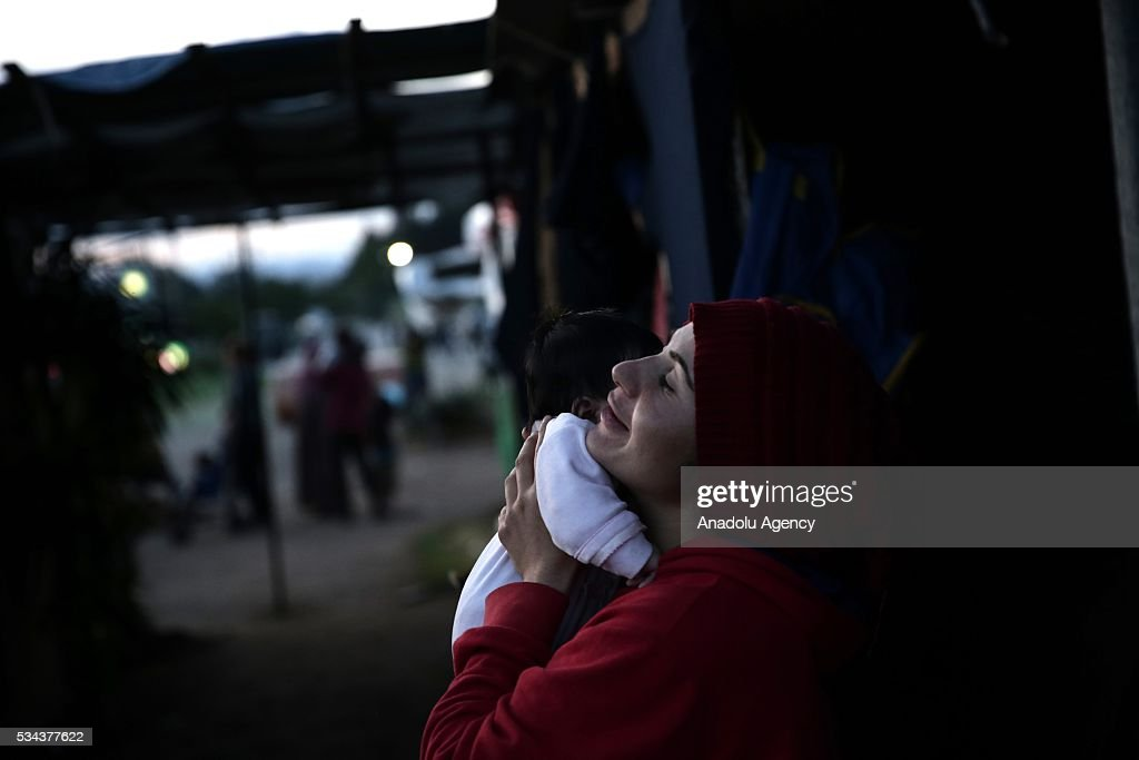 A refugee woman, escaping from the evacuation in Idomeni, holds her baby as they wait at another refugee camp near Idomeni, Greece on May 25, 2016.